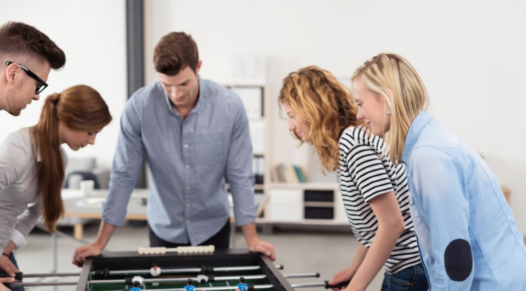 Young Office Workers Playing Table Football